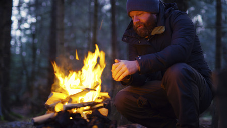 Man warms himself at camp fire in the forest