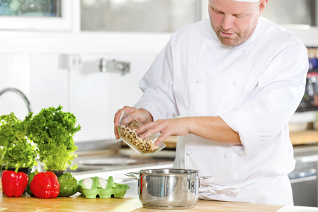 chef kitchen: Professional chef preparing food in large kitchen Stock Photo