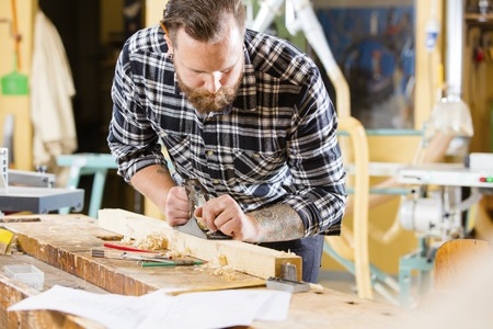 craftmanship: Carpenter work with plane on wood plank in workshop Stock Photo