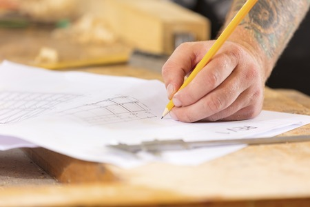 craftmanship: Close-up of carpenter plans project and writes at drawings in workshop