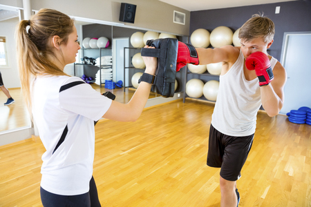 swiss ball: Boxer Punching Bag Held By Instructor In Gym