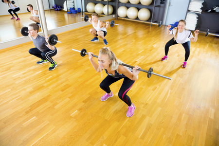 fitness gym: Friends in Group Lifting Barbell Rods In Fitness Gym