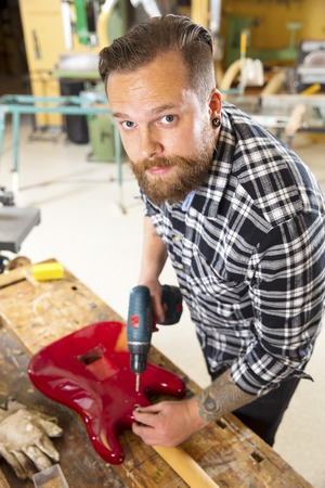 Environmental portrait of man working in workshop with guitar