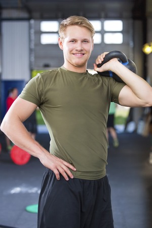 athleticism: Confident Fit Male Athlete Holding Kettlebell In Health Club