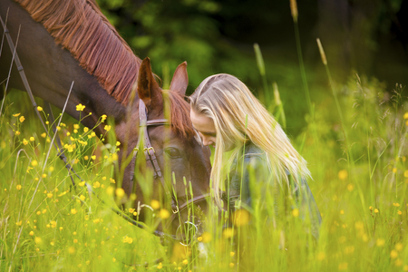 Smiling woman sitting in the meadow with her arabian horse