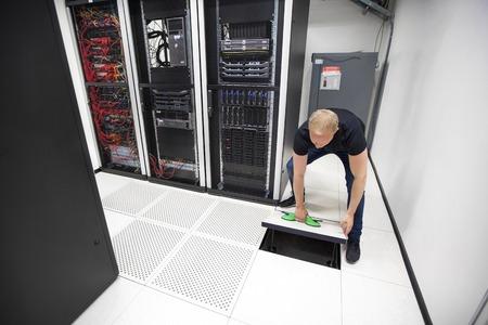 それは、データ センター内の吸引カップを使用して床タイルを持ち上げるエンジニア リングします。