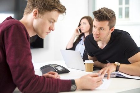 Businessmen Communicating While Colleague Using Smart Phone