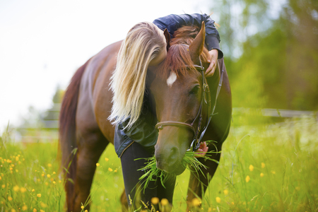 Blonde woman standing in a meadow hugging her arabian horse Stock Photo
