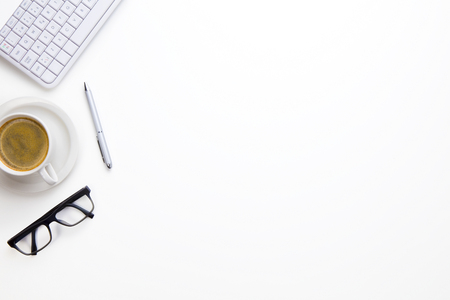 Keyboard With Eyeglasses, Coffee Cup And Pen On White Desk Stock Photo