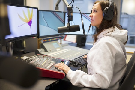 Jockey Using Headphones And Microphone While Looking At Monitor Stock Photo