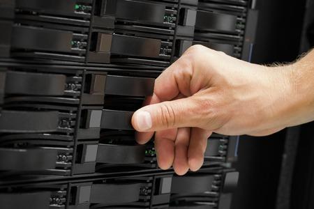 Computer Technicians Hand Replacing Hard Drive In San Stock Photo