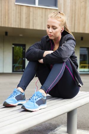 Relaxed Woman In Sportswear Listening To Music On Bench