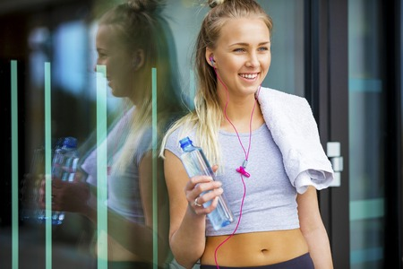 Smiling Fit Woman With Water Bottle Leaning Against Glass Wall