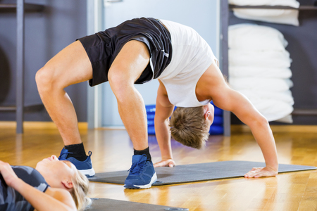 Man Performing Backbend Pose On Mat In Gym