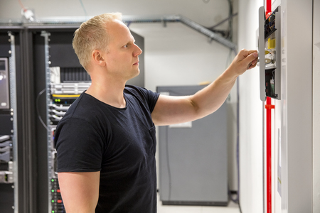 Confident Male Technician Opening Fire Panel In Datacenter Stock Photo