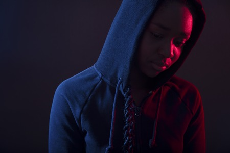 Colorful portrait of thoughtful woman with dark skin wearing hoodie Stock Photo
