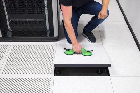 low section: Computer Engineer Pulling Floor Tile Using Suction Cups In Datac