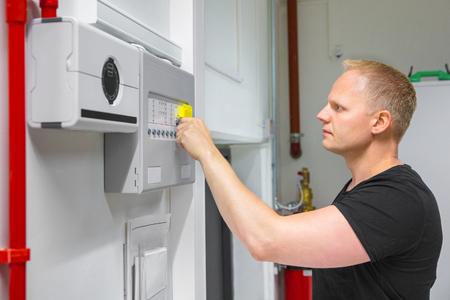 Male Technician Opening Fire Panel In Data Center