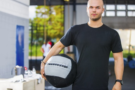 Confident Male Athlete Holding Medicine Ball In Health Club Stock Photo