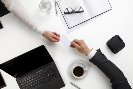Business Colleagues Exchanging Visiting Card At Office Desk