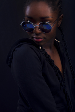 Cool young woman with dark skin wearing round sunglasses Stock Photo