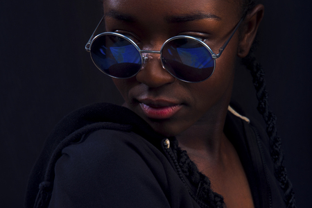Close-up of woman with dark skin wearing round sunglasses