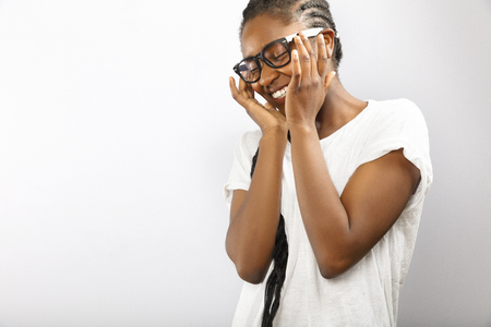 Happy and smiling african woman with glasses in white shirt Stock Photo