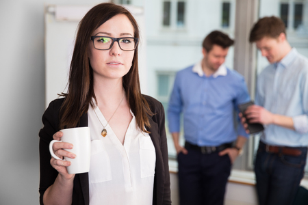 Businesswoman Holding Coffee Mug While Colleagues Discussing In Stock Photo