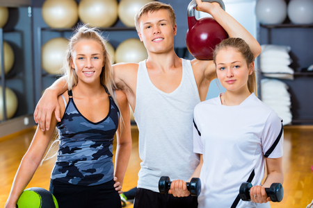 Confident Friends Lifting Weights In Gym
