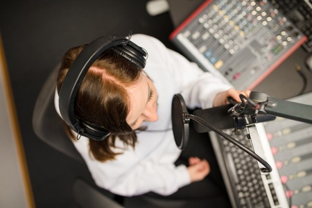 Directly Above Shot Of Radio Jockey Using Microphone And Headpho