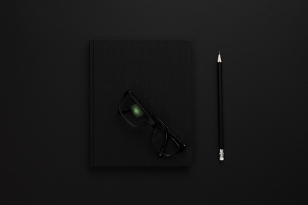 Top view of low key black office desk with notebook and supplies