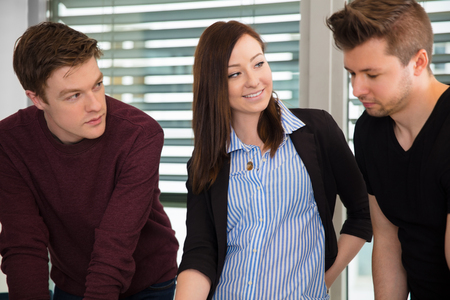 Smiling Businesswoman With Male Colleagues In Office