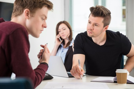 Professionals Planning While Colleague Using Mobile Phone In Off