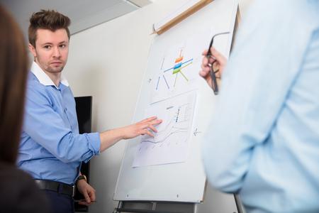 Businessman Touching Document On Flipchart While Giving Presenta Stock Photo
