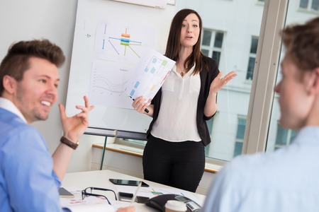 Female Professional Giving Presentation To Male Colleagues