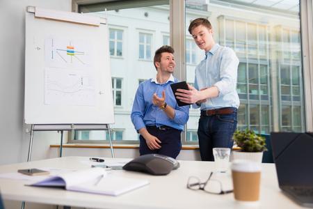 Businessmen Communicating Over Digital Tablet Against Window Stock Photo