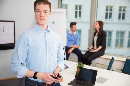 Businessman Standing While Colleagues Sitting On Window Sill Stock Photo