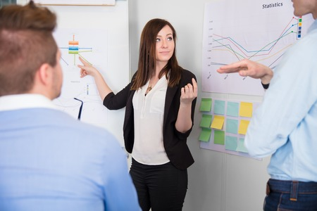 Businesswoman Communicating With Colleague While Pointing At Cha