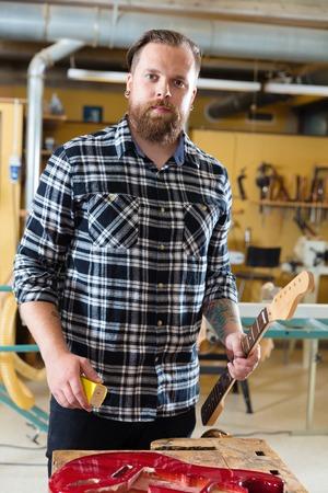 Carpenter work on a wooden guitar neck in workshop
