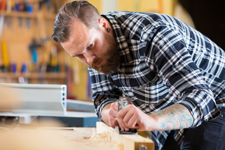 Carpenter works with plane on wood plank in workshop