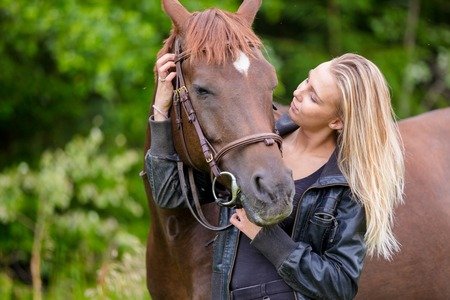 Young woman with her arabian horse standing in the field