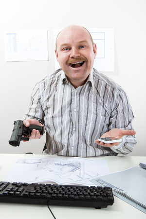 Funny Man Holding Handgun And Mobile Phone At Desk Stock Photo