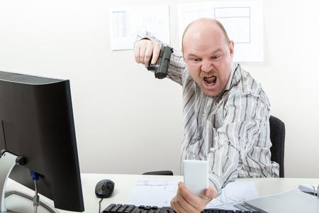 Businessman Aiming Gun On Mobile Phone At Desk Stock Photo
