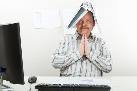Architect With Folder On Head Praying At Desk Stock Photo