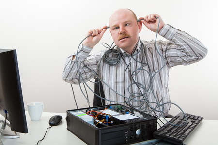 Businessman Touching Cables On Head While Repairing Computer Stock Photo