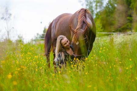Beautiful woman feeding her arabian horse in the field