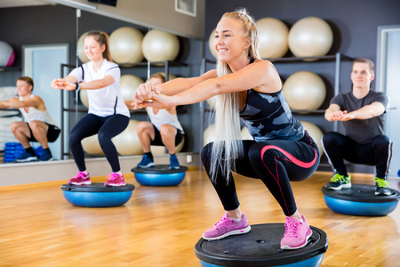 Focused and cheerful group training squats on half ball at fitness gym Stock Photo