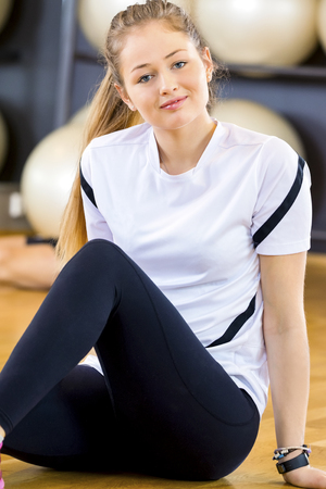 Smiling young woman in workout outfit at the fitness gym