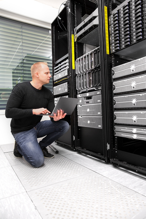 Male Consultant Using Laptop While Monitoring Servers In Datacen