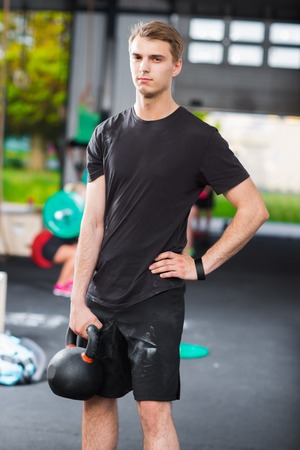 Confident Gym Instructor Holding Kettlebell In Health Club